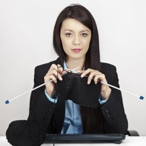 professional woman sitting at her desk, knitting