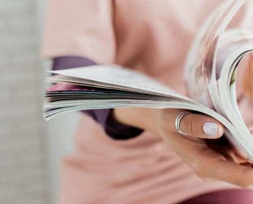Close-up of a woman thumbing through catalog mindlesssly creating discontentment