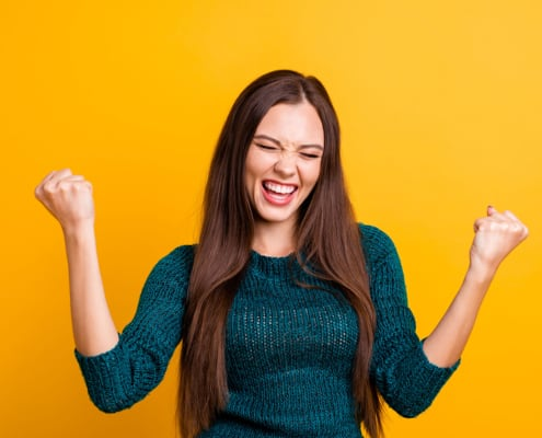 Close up photo beautiful yelling her she lady eyes closed open toothy mouth arms fists raised up air brown eyes ecstatic wear green knitted pullover jumper clothes isolated yellow background