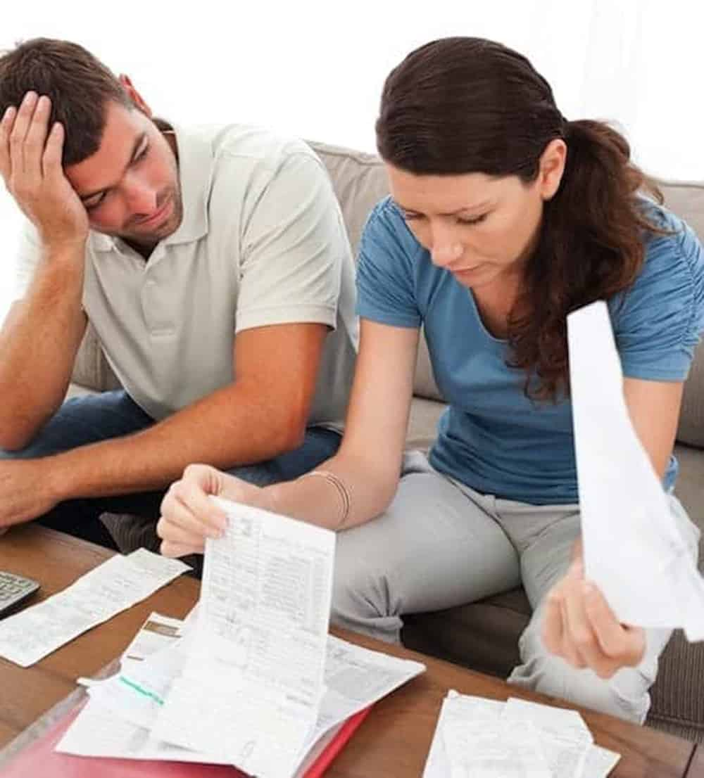 Couple stressed and worried looking at bills