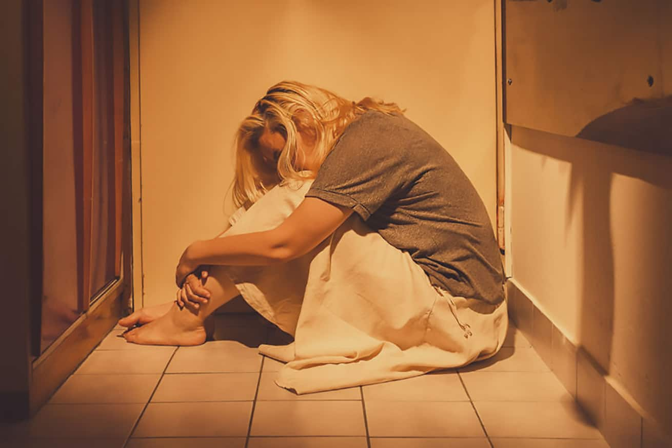 ad, depressed and lonely woman sitting in a corner on a floor tiles, in a skirt, barefoot with a long blond hair