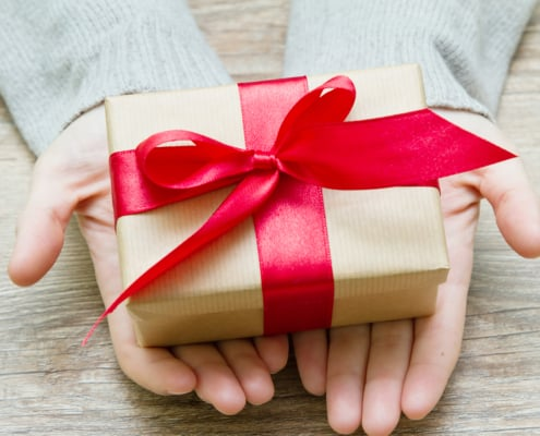 hands holding small Christmas gift in kraft paper and red bow