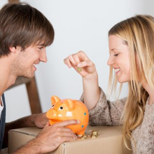 couple moving and thowing coins in a piggybank